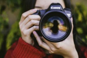 Femme tenant un appareil photo jusqu'à son visage