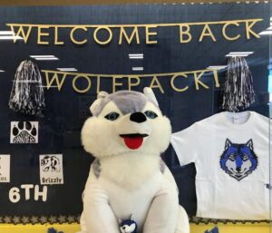 Image of stuffed animal wolf, with display case in the back that says Welcome Back Wolfpack